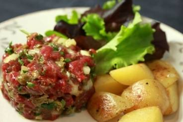 Steak tartare with sautéed potatoes, mayonnaise and dressed leaves