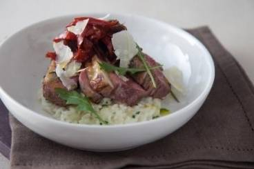 Garlic and rosemary studded rump of lamb with herb risotto, red pepper chutney and pea shoots Recipe
