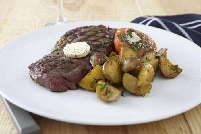 Sirloin steak with garlic butter, herb roasted tomatoes and pan fried potatoes Recipe