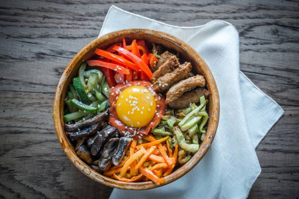 Bi bim bap, a popular Korean rice dish with sautéed vegetables, Korean paste topped with a fried egg and sliced beef. Recipe